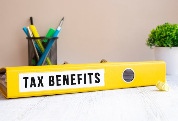 Uma pasta amarela com o rótulo benefícios fiscais está na mesa do escritório. fundo de flores e artigos de papelaria. conceito financeiro.