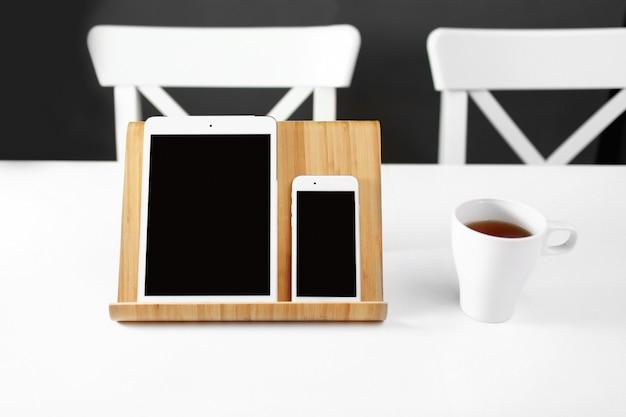 Uma pastilha branca e um smartphone em um suporte em um local de trabalho de escritório de mesa branca. uma caneca de chá no local de trabalho