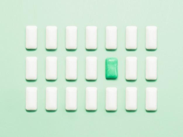 Uma pastilha elástica verde que está fora das pastilhas elásticas brancas.