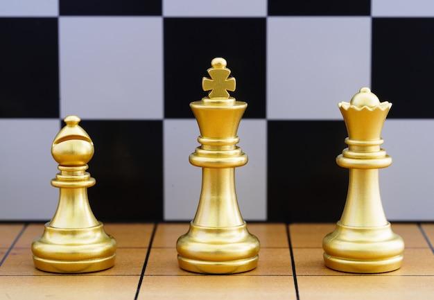 Uma peça de xadrez do rei de ouro e várias peças de xadrez estão em um tabuleiro de xadrez de madeira tegy