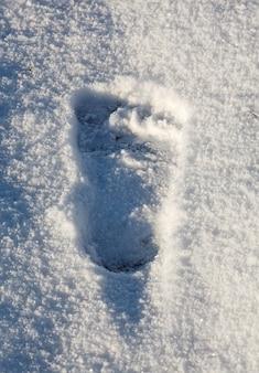 Uma pegada de pés descalços na neve