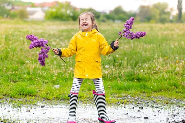 Uma pequena alegre linda garota com botas de borracha fica em uma poça e tem flores lilás nas mãos.