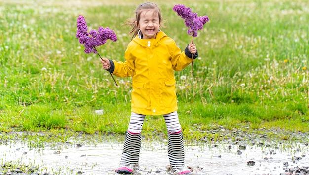 Uma pequena alegre linda garota em uma capa de chuva amarela e botas de borracha está em uma poça e tem flores lilás nas mãos.