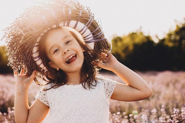Uma pequena alegre menina caucasiana usando uma coroa de flores está brincando feliz sob o calor do sol