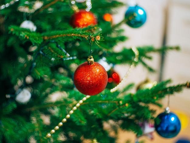Uma pequena árvore de natal em uma panela decorada com guirlandas de bolas