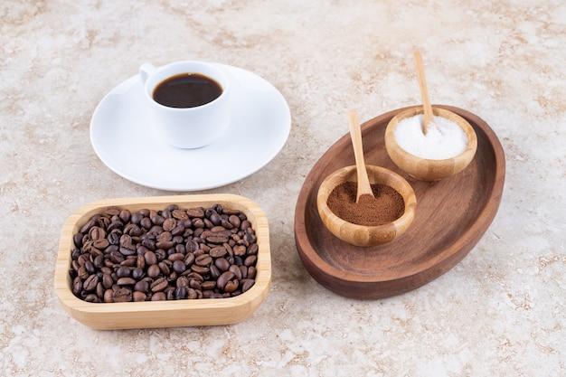 Uma pequena bandeja com tigelas de açúcar e pó de café moído ao lado de uma xícara de café e uma tigela de grãos de café