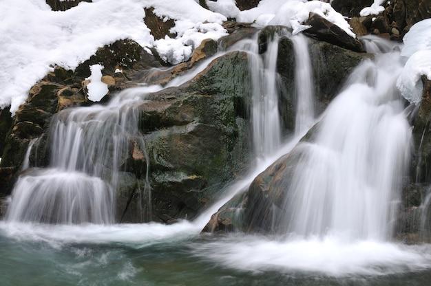 Uma pequena cachoeira ativa córrego da montanha limpa neve inverno paisagem vida selvagem fundo