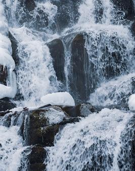 Uma pequena cachoeira na montanha de água gelada flui entre pedras úmidas cobertas de neve branca