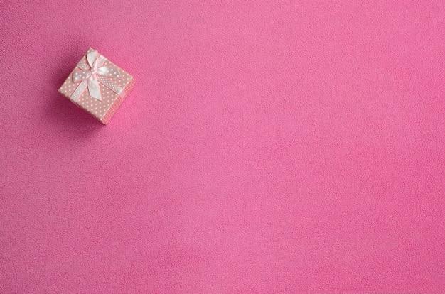Uma pequena caixa de presente em rosa com um pequeno laço encontra-se em um cobertor de tecido de lã rosa claro macio e peludo