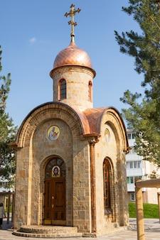 Uma pequena capela da cidade feita de pedra com banhos dourados e ícones localizados no parque da cidade.