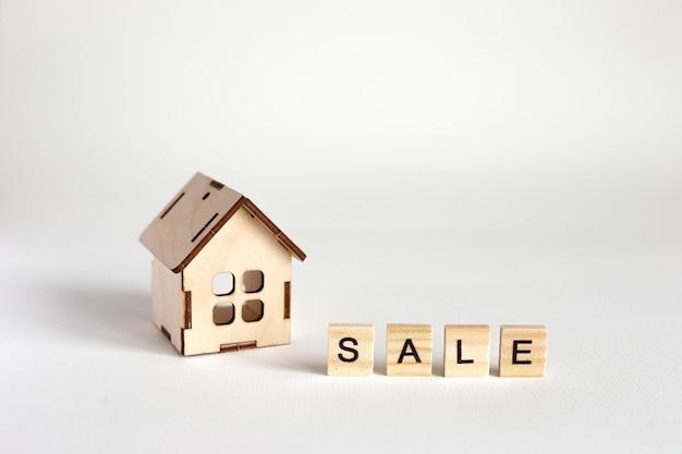 Uma pequena casa de brinquedo de madeira, fica em um fundo branco e uma inscrição de venda de letras de madeira. copie o espaço. fechar-se
