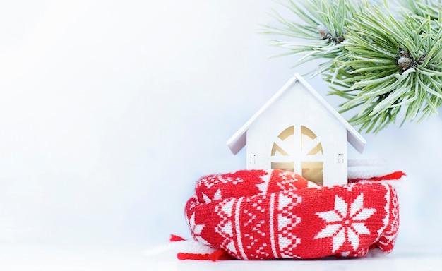 Uma pequena casa em um lenço sob um galho de pinheiro. conceito de aquecimento