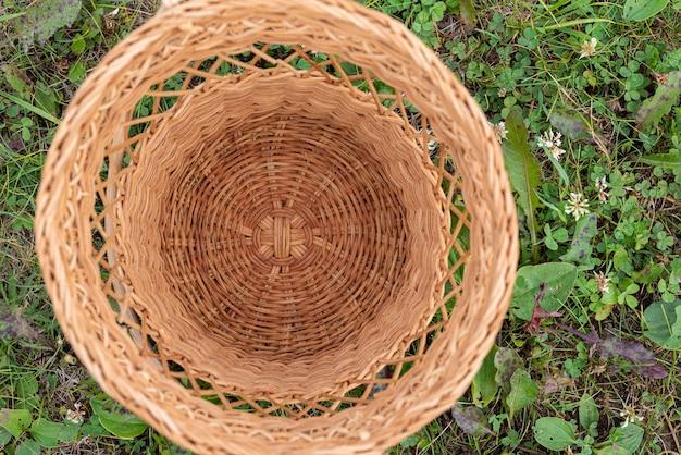 Uma pequena cesta de vime vazia na grama no meio de um parque florestal