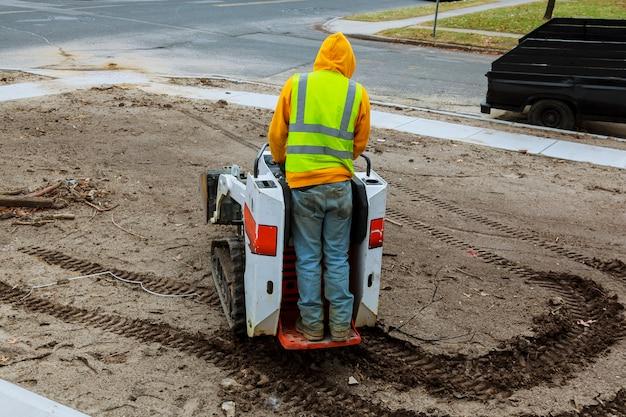 Uma pequena escavadeira trabalha na rua no verão