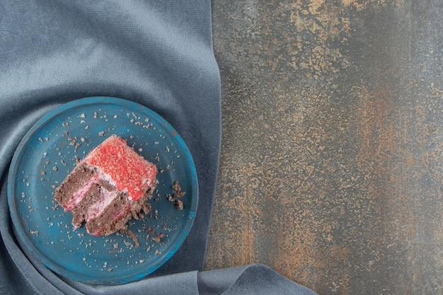 Uma pequena fatia de bolo em uma travessa azul em um pedaço de tecido