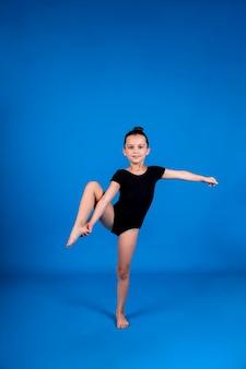 Uma pequena ginasta em um maiô preto realiza um exercício de alongamento sobre um fundo azul com uma cópia do espaço