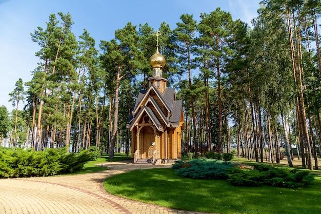 Uma pequena igreja de madeira com cúpula dourada no meio de uma área verde com caminhos de tijolos