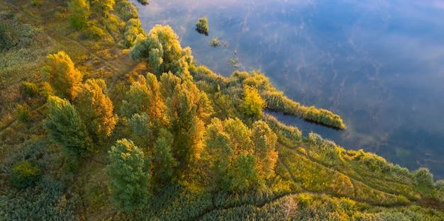 Uma pequena ilha no lago com árvores amarelas de outono.