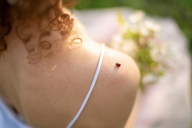 Uma pequena joaninha está sentada no ombro de uma jovem mulher