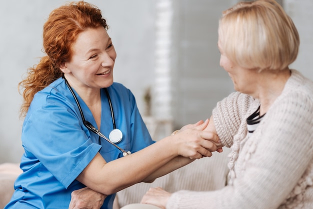 Uma pequena massagem. bem humorado, enérgico especialista excelente ajudando seu paciente idoso em casa enquanto ela sentia uma dor no cotovelo e pedia tratamento