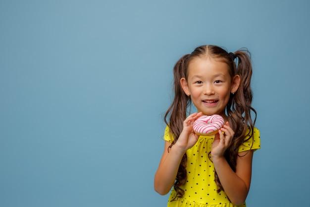 Uma pequena menina asiática com cabelo comprido segura um donut nas mãos e sorri no estúdio em um azul