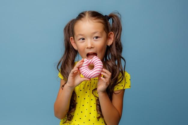 Uma pequena menina asiática com cabelo comprido segura um donut nas mãos e sorri