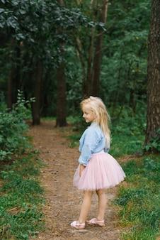 Uma pequena menina loira de cinco anos em roupas românticas caminha por um caminho na floresta e sorri