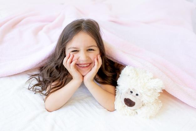 Uma pequena menina sorridente de 5-6 anos está deitada na cama com um ursinho de pelúcia, as mãos sob as bochechas