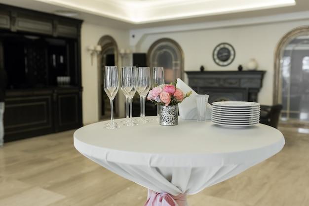 Uma pequena mesa auxiliar no restaurante, na qual há copos e pratos vazios.