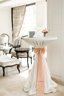 Uma pequena mesa auxiliar no restaurante, na qual há copos e pratos vazios