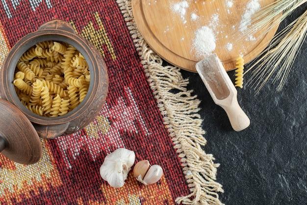 Uma pequena panela de macarrão espiral não preparado com alho e farinha