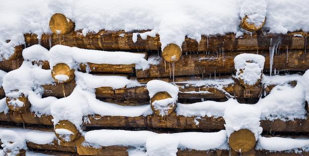 Uma pequena parede de pequenas toras no fundo sob a neve no inverno