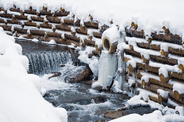 Uma pequena parede de pequenos troncos envolve um pequeno riacho na montanha com cachoeiras em uma floresta de inverno perto de árvores nuas nas montanhas dos cárpatos