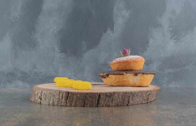 Uma pequena pilha de bolos e marmeladas em uma placa de madeira