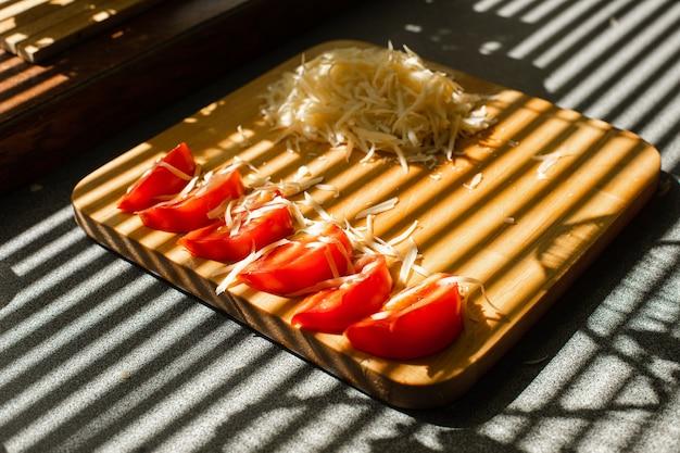 Uma pequena pilha de queijo fresco ralado e tomates vermelhos repousa sobre uma placa de madeira na cozinha