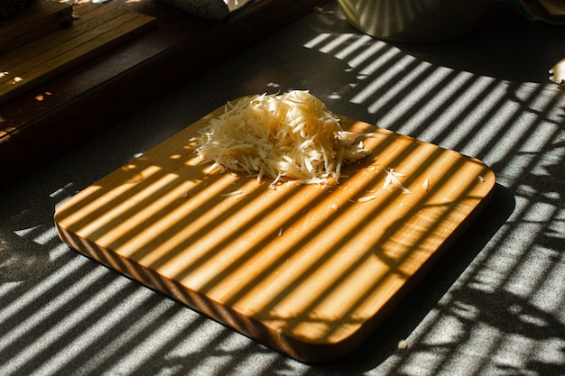 Uma pequena pilha de queijo fresco ralado está em uma placa de madeira na cozinha