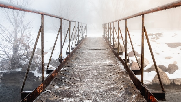 Uma pequena ponte de metal sobre um riacho saindo no meio do nevoeiro.