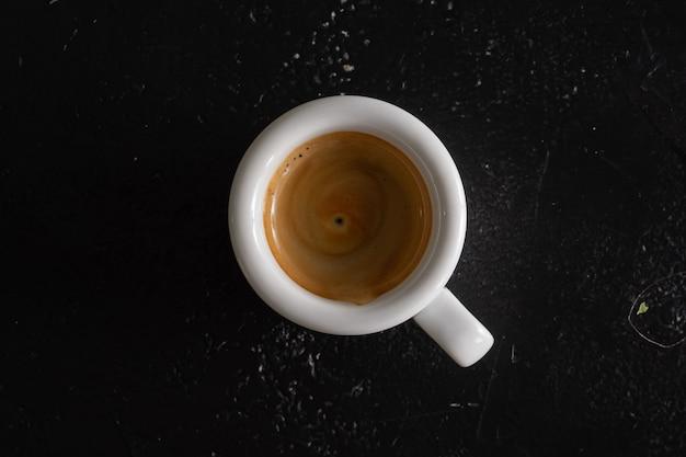 Uma pequena porção de café ristretto forte em uma xícara branca.