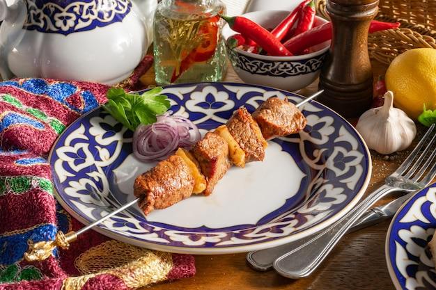 Uma pequena porção de shish kebab de cordeiro no espeto com cebola roxa e salsa em um prato com padrão nacional uzbeque
