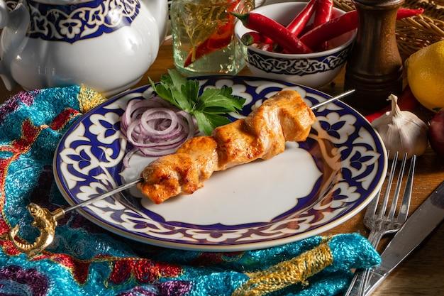 Uma pequena porção de shish kebab de frango no espeto com cebola roxa e salsa em um prato com padrão nacional uzbeque