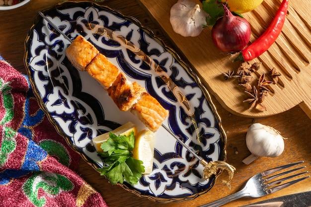 Uma pequena porção de shish kebab de salmão com limão e salsa em um prato com um padrão tradicional uzbeque