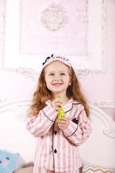 Uma pequena ruiva vestida de pijama rosa está brincando com bolhas no quarto na cama grande