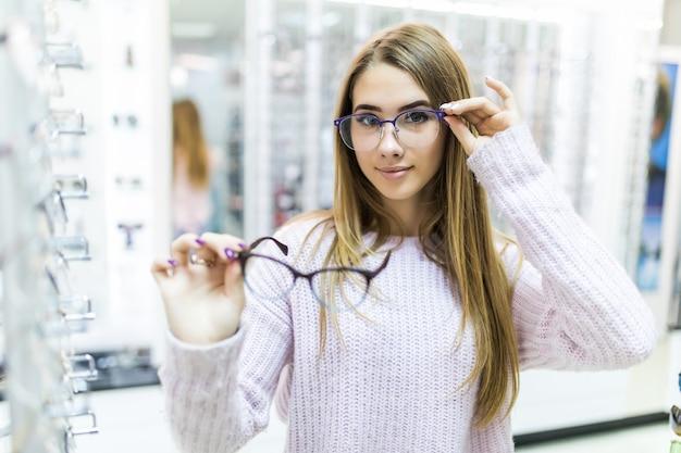 Uma pequena senhora vestida com um suéter branco segura óculos médicos no braço e os observa em uma loja especial