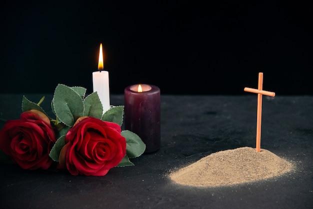 Uma pequena sepultura com velas e flores como memória na superfície escura