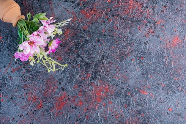Uma pequena tigela de barro com buquê de flores em mármore