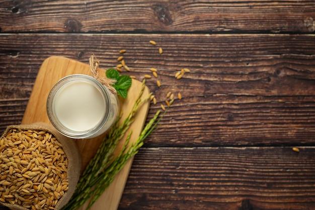 Uma pequena tigela de leite de arroz com arroz e sementes de arroz colocada no chão de madeira