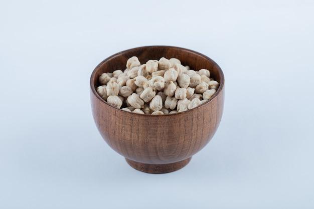Uma pequena tigela de madeira cheia de grãos de ervilhas brancas crus