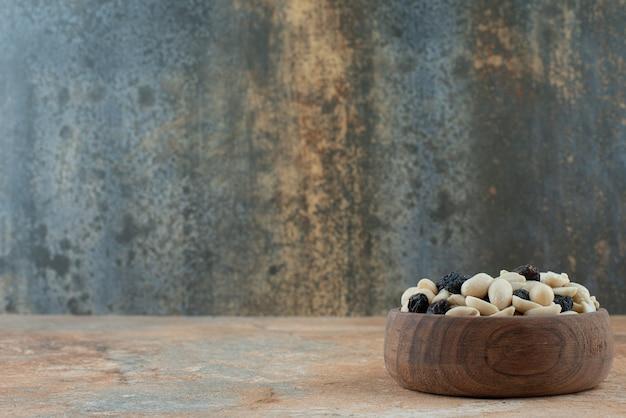 Uma pequena tigela de madeira cheia de passas e nozes em fundo de mármore