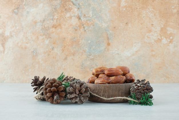 Uma pequena tigela de madeira com frutas secas e pinhas no fundo de mármore. foto de alta qualidade