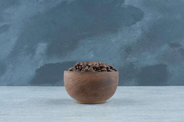 Uma pequena tigela de madeira com grãos de café no fundo branco. foto de alta qualidade